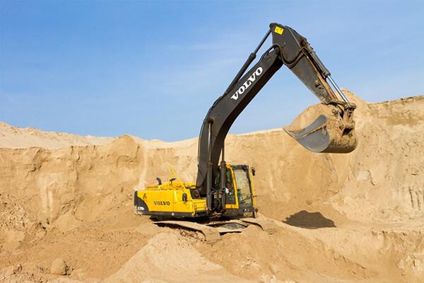 Экскаватор копает песчаный карьер